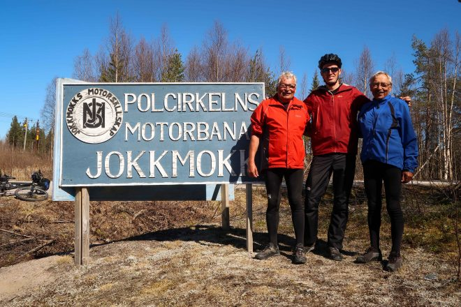 Three men stand at the Polar Circle in Jokkmokk, Sweden