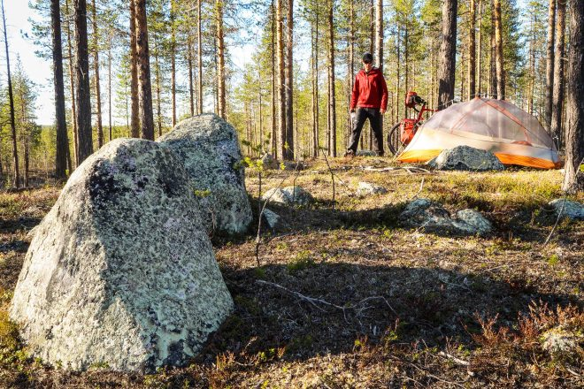Forest stones greet bicycle tourist pitching tent