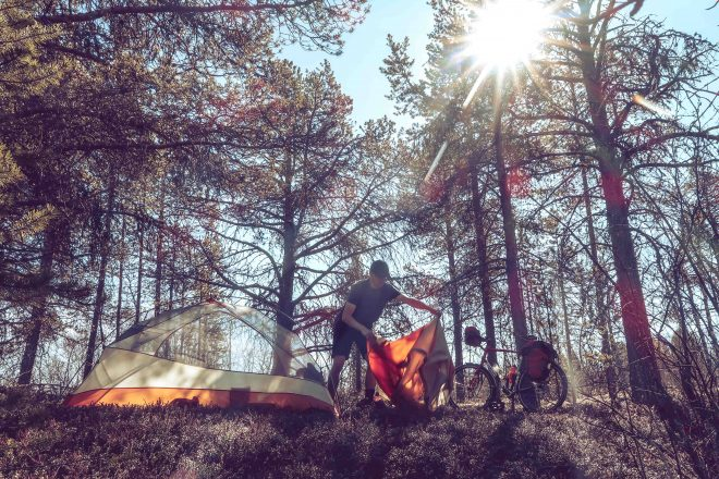camper pitching tent in sunny forest in finland