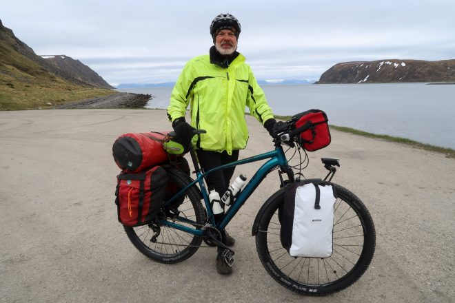 Retired German man with fully loaded touring bicycle in Norway