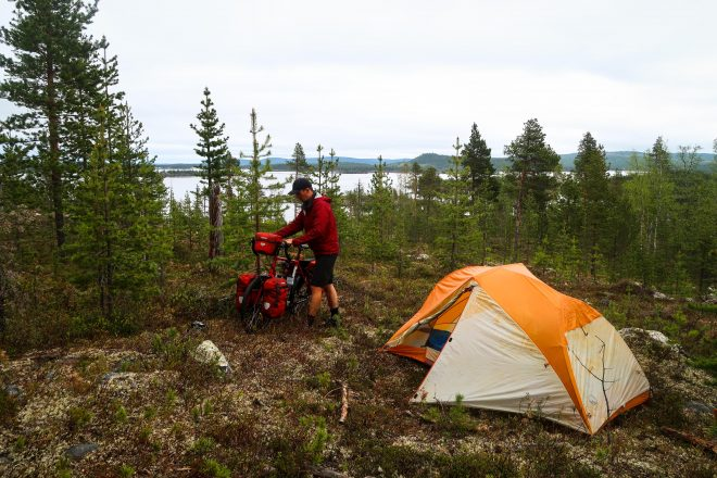 Bicycle camping on a mountain above a lake in Finland