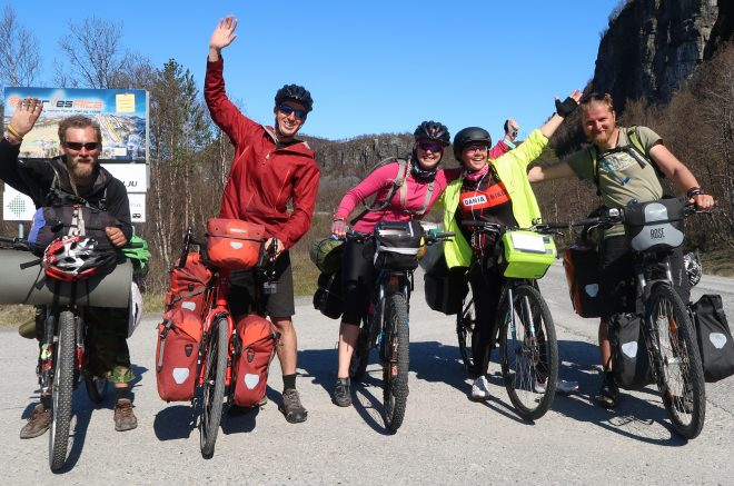 Andris, Darren, June, Vanja and Artis standing with their loaded touring bicycles