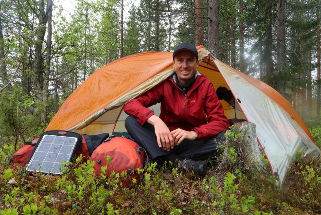 Darren Alff smiling while camping in tent in Finland