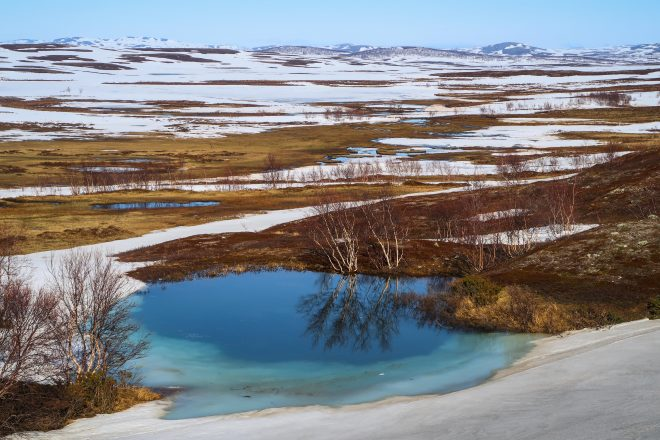 Frozen blue pond in nordkapp snowy arctic region