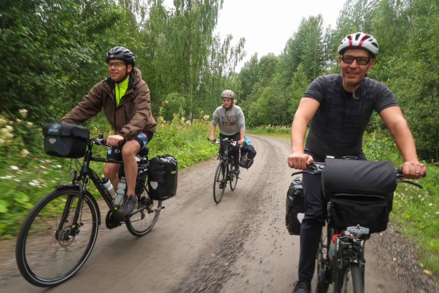 Three male and female bicycle tourists riding on dirt road