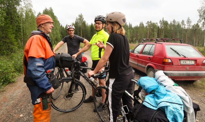 Old lumber worker talks with group of bicycle tourists