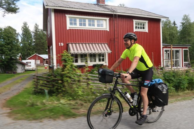 Red house and yellow cyclist in Sweden