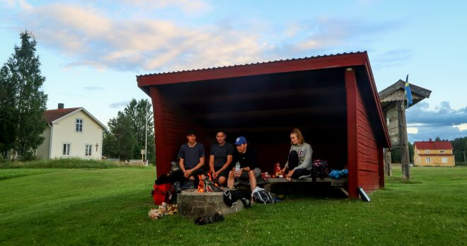 Four bicycle tourists sit inside free shelter in northern Sweden