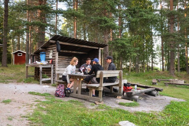 Four campers sit at picnic table in front of campfire shelter in Pitea, Sweden