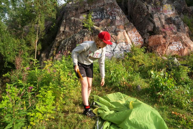 Blonde girl in red hat setting up her tent