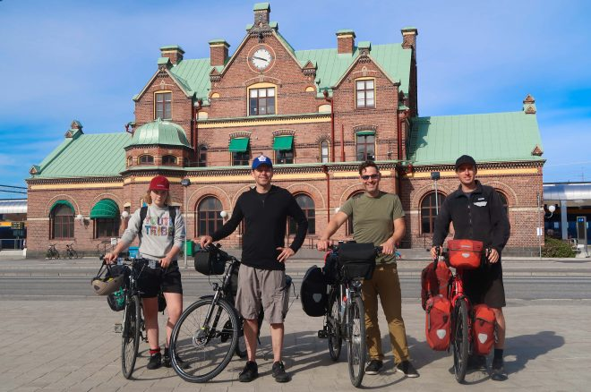 Four male and female bicycle travelers standing with their bikes in front of the Umea, Sweden train station
