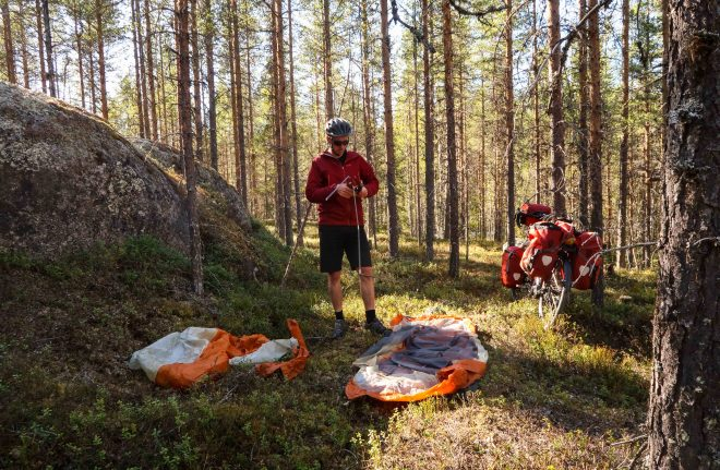 Adventure cyclist pitching tent in Swedish forest
