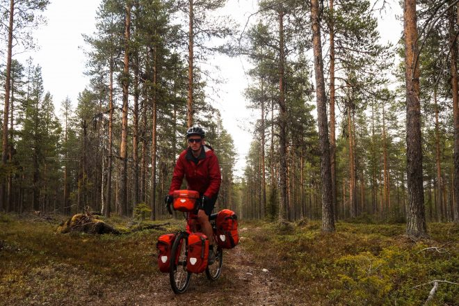 Bicycle Touring Pro red bike in Swedish green forest