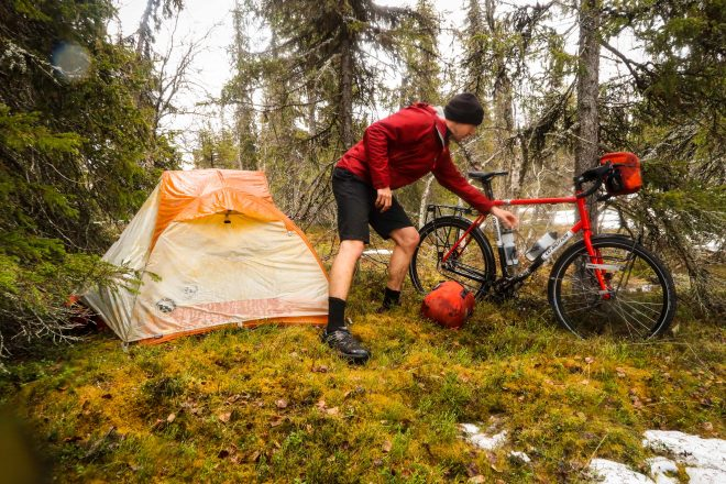 Darren Alff reaches for water bottle on his bicycle with tent in background