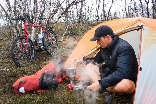 Bicycle traveler Darren Alff cooks dinner on a camp stove sitting outside his tent in lapland norway