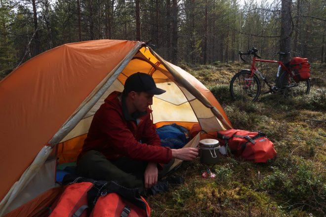 Bicycle Touring Pro cooks dinner in the forests of Sweden in his tent with Co-Motion Siskiyou touring bicycle leaning against tree in background