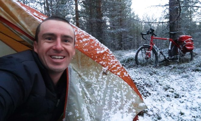 Darren Alff peeks his head outside his tent to discover that it has snowed overnight while on his 2017 bike tour across northern Europe