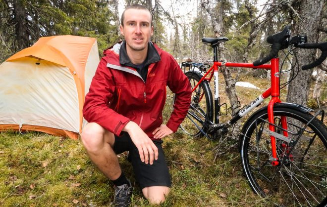 Darren Alff kneeling next to his Big Agnes Copper Spur UL 1 tent and Co-Motion Cycles Siskiyou touring bicycle in Sweden