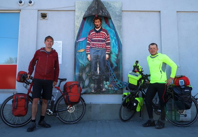 Andreas and the Bicycle Touring Pro stand together with a fisherman mural in Alta Norway