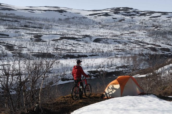 Bicycle Touring Pro standing with his bike and tent on a cliff overlooking a snow-covered mountain with a river running below him
