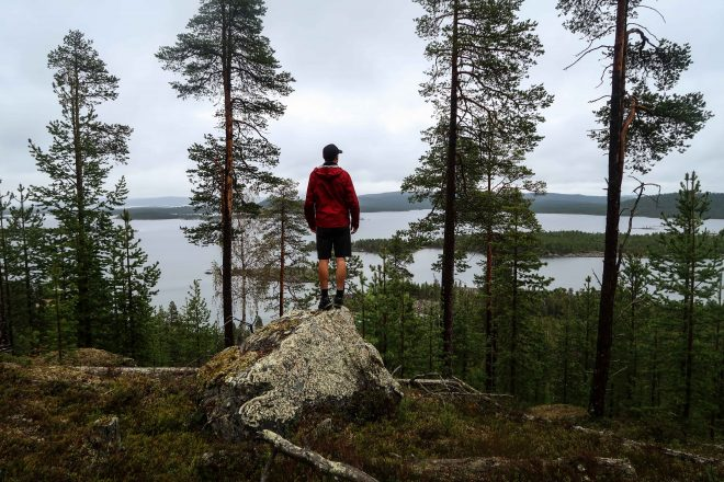 Man in red jacket standing on a rock and looking out over a lake in northern Finland