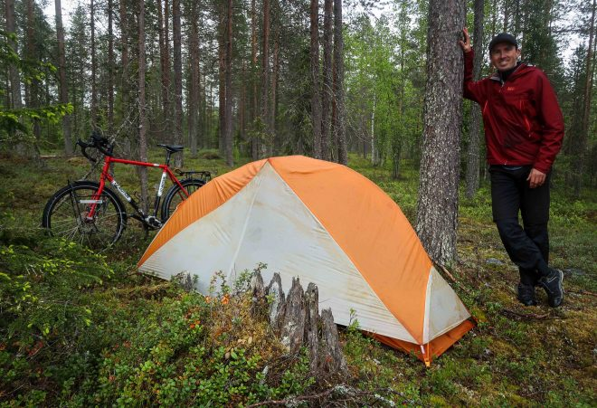 Darren Alff standing next to a tree and his touring bicycle and tent