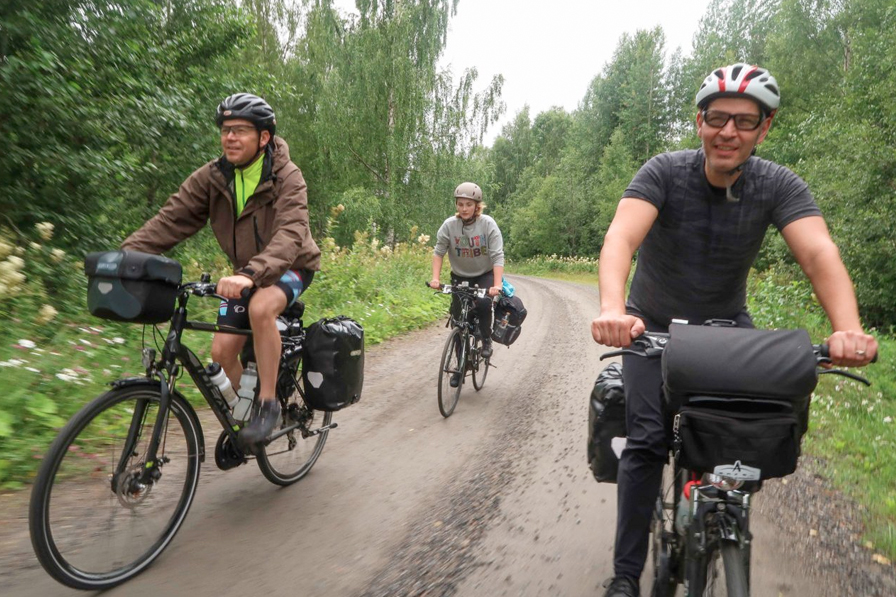 three bicycle tourists on dirt road