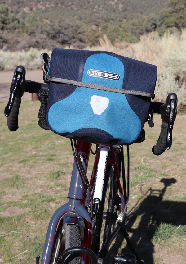 blue ortlieb ultimate 6 handlebar bag on touring bicycle
